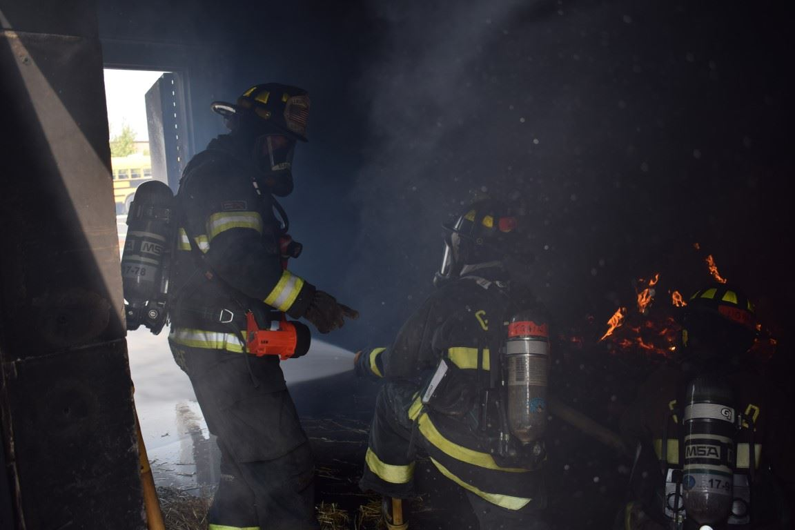 Interior of building on fire with three firemen inside