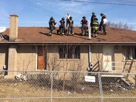 Ten firemen on roof of one story home