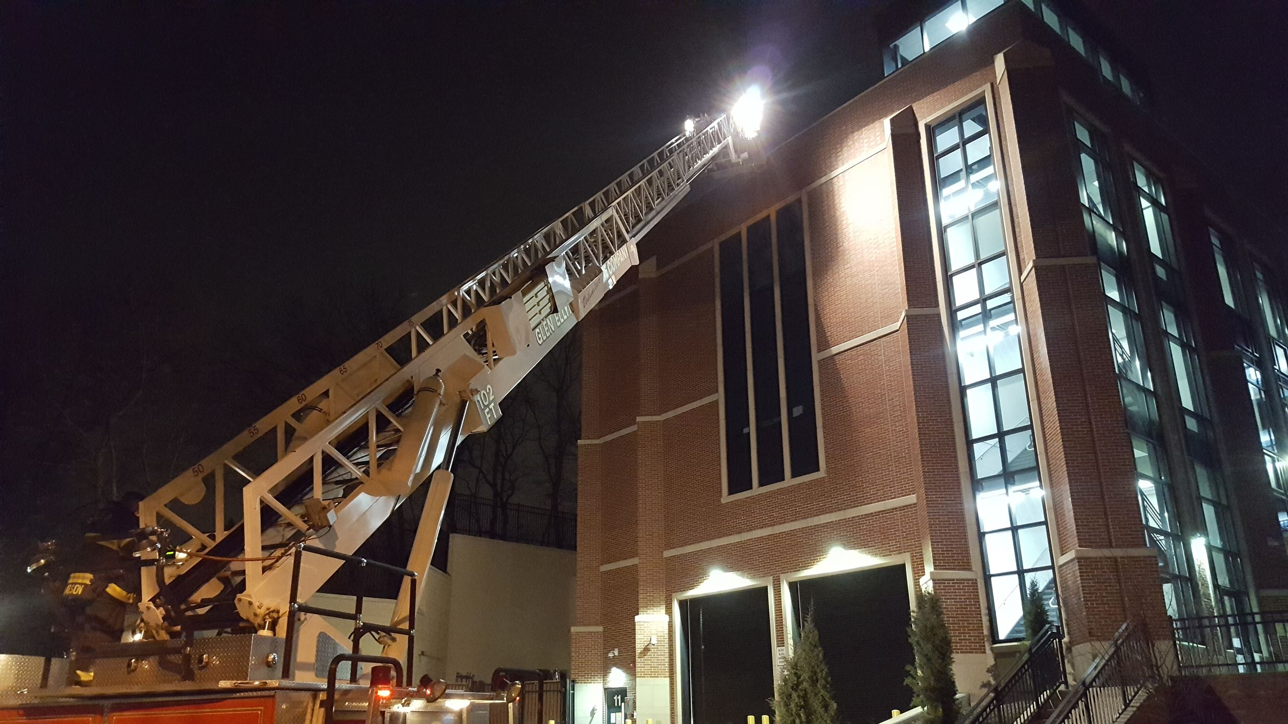 Ladder of fire truck up against training building